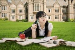 La colegiala china aprende en el parque Imagenes de archivo