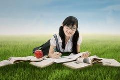 La colegiala china atractiva aprende en el campo Foto de archivo libre de regalías