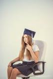 La colegiala con el graduado del casquillo se sienta en la silla, pensando en futuro Imagen de archivo libre de regalías