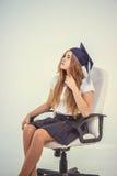 La colegiala con el graduado del casquillo se sienta en la silla, pensando en futuro Imágenes de archivo libres de regalías