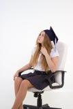 La colegiala con el graduado del casquillo se sienta en la silla, pensando en futuro Foto de archivo