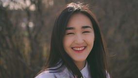 La colegiala coreana joven mira la cámara y la sonrisa agradable Mujer feliz y buena almacen de metraje de vídeo