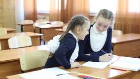 La colegiala de las muchachas se mira furtivamente en un cuaderno almacen de video