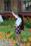 La colegiala de la muchacha con el pelo largo en uniforme escolar hace el selfie foto de archivo