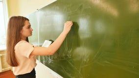 La colegiala de la muchacha escribe en las fórmulas matemáticas de la pizarra Imagen de archivo libre de regalías