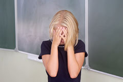 La colegiala del niño cubrió su cara con sus manos en la sala de clase cerca del tablero No aprendió una lección o un trastorno E Imagen de archivo