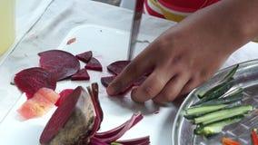 La colegiala elemental corta el rábano rojo mientras que ella compite en la competencia de cocinar anual almacen de metraje de vídeo