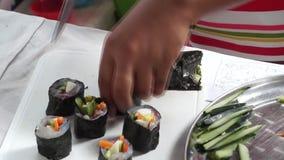 La colegiala elemental corta el rollo de sushi de los pescados mientras que ella compite en la competencia de cocinar anual almacen de video