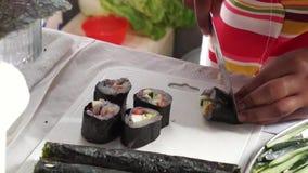 La colegiala elemental corta el rollo de sushi de los pescados mientras que ella compite en la competencia de cocinar anual almacen de metraje de vídeo