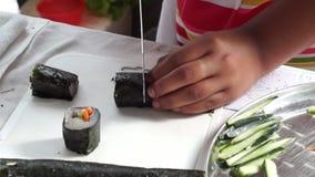 La colegiala elemental corta el rollo de sushi de los pescados mientras que ella compite en la competencia de cocinar anual metrajes