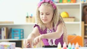 La colegiala elemental dibuja La muchacha cambia el lápiz del color en el otro metrajes