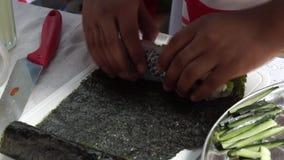 La colegiala elemental envuelve el rollo de sushi de los pescados mientras que ella compite en la competencia de cocinar anual almacen de metraje de vídeo