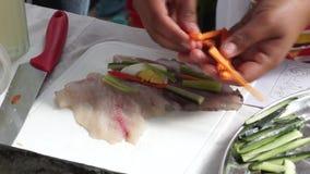 La colegiala elemental rellena el rollo de sushi de los pescados mientras que ella compite en la competencia de cocinar anual almacen de video