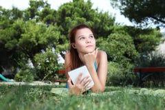 La colegiala en el parque con el libro de e, mira para arriba Imágenes de archivo libres de regalías