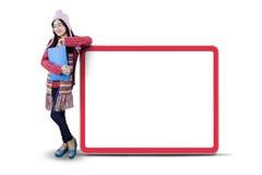La colegiala en ropa caliente se inclina en la cartelera Fotografía de archivo libre de regalías