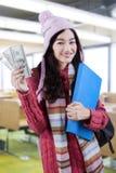 La colegiala en suéter hecho punto sostiene el dinero Imagenes de archivo