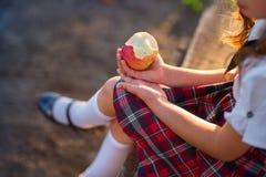 La colegiala en uniforme está comiendo una manzana en el parque foto de archivo