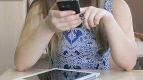La colegiala escribe el mensaje usando el teléfono móvil almacen de metraje de vídeo