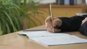 La colegiala escribe el texto en cuaderno usando el lápiz almacen de metraje de vídeo