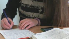 La colegiala escribe el texto en la hoja de papel blanca almacen de video