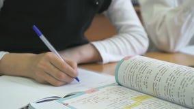 La colegiala escribe en cuaderno con el bolígrafo almacen de metraje de vídeo