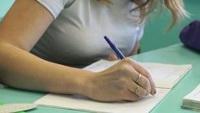 La colegiala escribe en cuaderno en la lección almacen de video