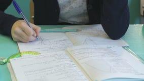 La colegiala escribe en su cuaderno en la lección almacen de metraje de vídeo