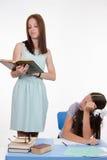 La colegiala escucha un profesor aburrido Foto de archivo