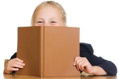 La colegiala está ocultando detrás de un libro Foto de archivo libre de regalías