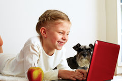 La colegiala estudia en casa en un ordenador portátil Fotografía de archivo