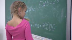 La colegiala feliz con tiza soluciona ejemplos en matemáticas en la pizarra del verde de la escuela durante una lección en la cla almacen de video