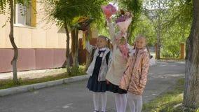 La colegiala feliz que aumenta las manos para arriba con el ramo florece De nuevo a concepto de la escuela almacen de video