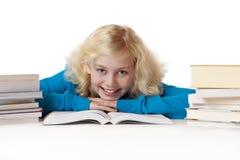 La colegiala feliz que miente en suelo y aprende Imagen de archivo libre de regalías