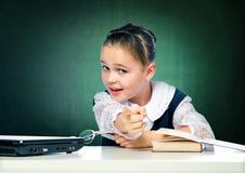 La colegiala hace las lecciones que se sientan detrás de un escritorio Fotografía de archivo