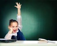 La colegiala hace las lecciones que se sientan detrás de un escritorio Foto de archivo