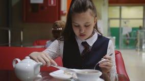 La colegiala hambrienta sola come en la cafeter?a de la escuela durante rotura almacen de metraje de vídeo