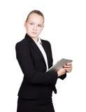 La colegiala hermosa en un traje de negocios celebra una tableta de la PC en sus manos y la mirada en la cámara Imagenes de archivo