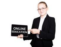 La colegiala hermosa en un traje de negocios celebra una tableta de la PC en sus manos y la mirada en la cámara, en una tableta d Imagen de archivo libre de regalías