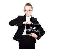 La colegiala hermosa en un traje de negocios celebra una tableta de la PC en sus manos y la mirada en la cámara, en una tableta d Imagenes de archivo