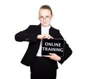 La colegiala hermosa en un traje de negocios celebra una tableta de la PC en sus manos y la mirada en la cámara, en una tableta d Fotografía de archivo