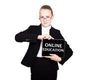 La colegiala hermosa en un traje de negocios celebra una tableta de la PC en sus manos y la mirada en la cámara, en una tableta d Imagen de archivo