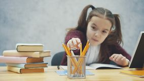 La colegiala inteligente, atenta realiza la preparación mientras que se sienta en la tabla Durante esta escritura, el lápiz toma metrajes