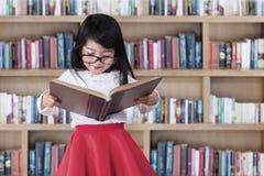 La colegiala lee el libro en biblioteca Fotos de archivo