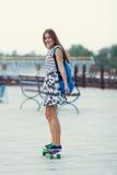 La colegiala linda joven monta el monopatín en el camino Imagen de archivo