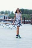 La colegiala linda joven monta el monopatín en el camino Fotografía de archivo libre de regalías