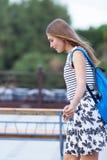 La colegiala linda joven monta el monopatín en el camino Imagenes de archivo