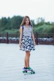 La colegiala linda joven monta el monopatín en el camino Fotos de archivo