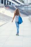 La colegiala linda joven monta el monopatín en el camino Fotos de archivo libres de regalías