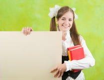 La colegiala lleva a cabo la lona en blanco Imagen de archivo