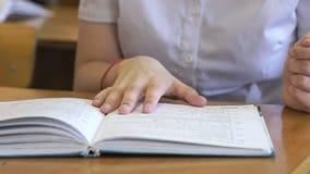 La colegiala mueve de un tirón las páginas del libro de escuela metrajes